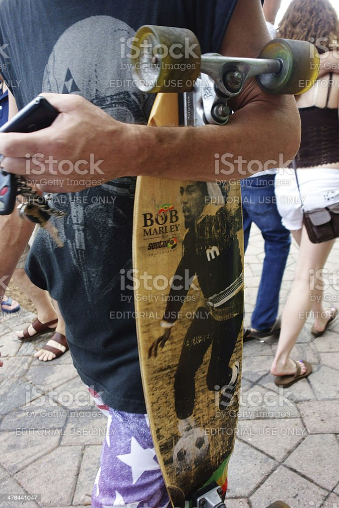 Young man with Bob Marley skateboard at street festival​​​ foto