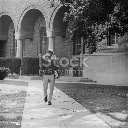 istock Young man with books walking on campus 120427750