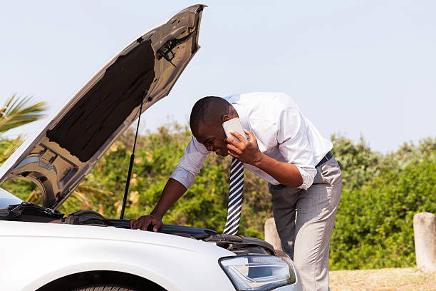 young man with broken down car calling for help​​​ foto