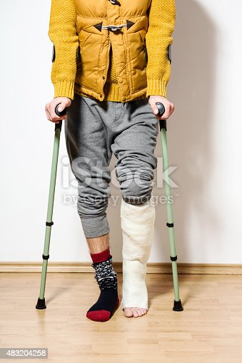 Young man with broken leg in plaster cast lying standing with crutches against wall. Close up of legs, unrecognizable person.