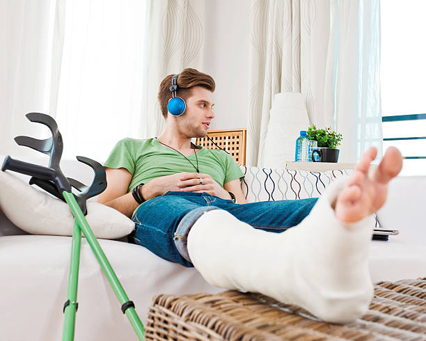 young man with broken leg at home - broken leg stock photos and pictures