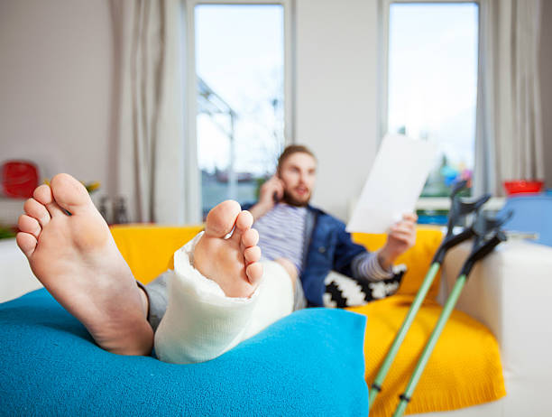 young man with broken leg using at home - broken leg stock photos and pictures