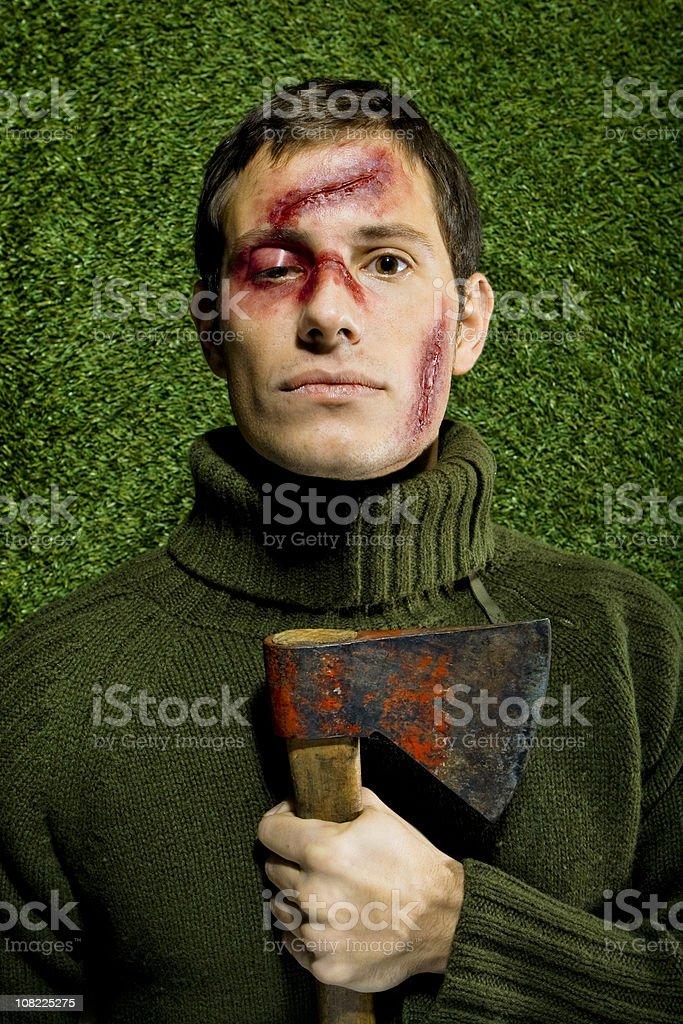 Jeune homme avec des bleus et des coupes sur visage tenant Hache - Photo