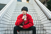 Portrait of a young modern Asian man sitting on stairs and holding tapioca milk tea.