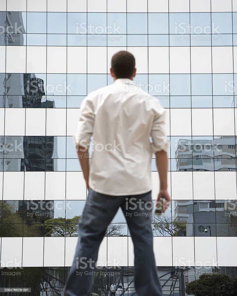 Young man with cell phone standing beside office building, rear view royalty-free stock photo
