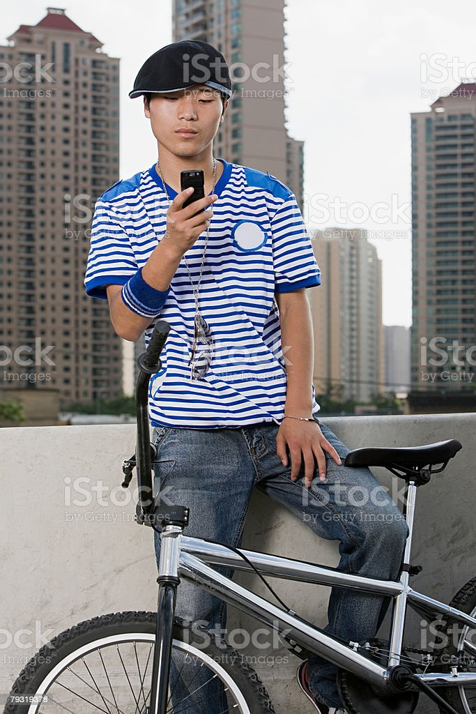 Young man with cellphone and bike 免版稅 stock photo