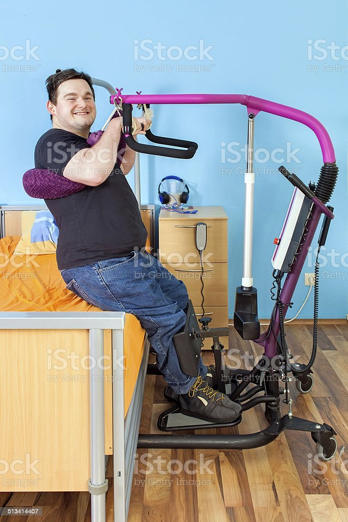 Young man with cerebral palsy using a patient lift. stock photo