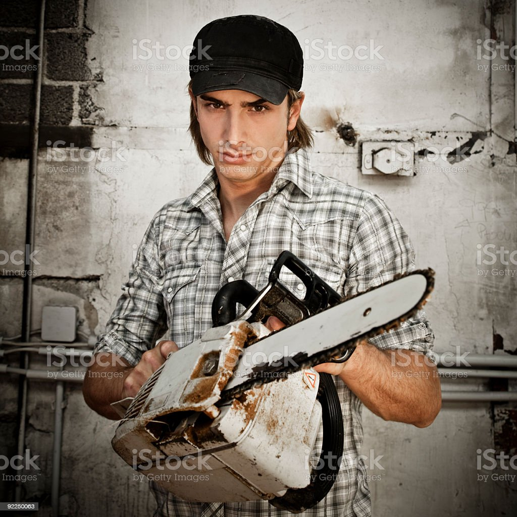 young man with chainsaw royalty-free stock photo