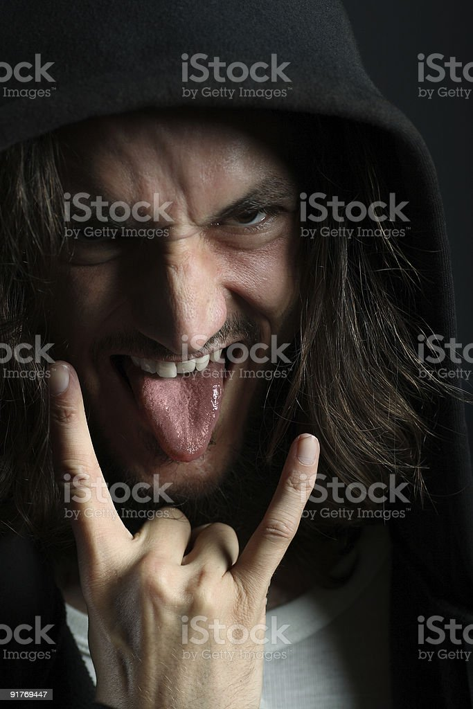 Young man with characteristic heavy metal tongue gesture royalty-free stock photo