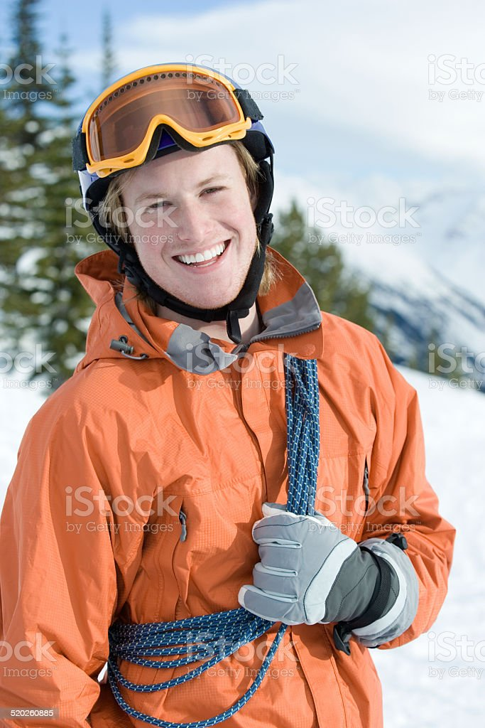 Young man with climbing rope and goggles in winter landscape stock photo