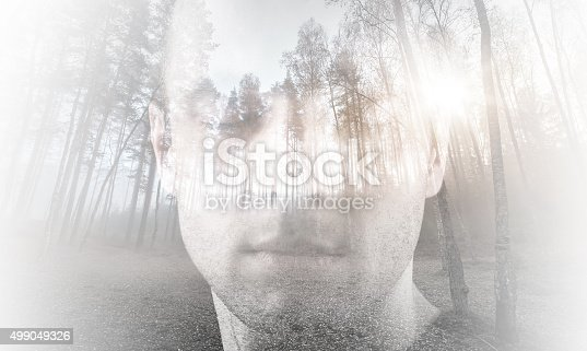 istock Young man with closed eyes combined with landscape 499049326