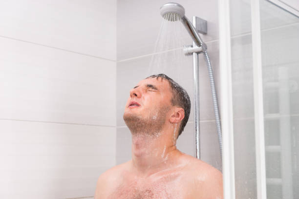 young man with closed eyes taking a shower - シャワー ストックフォトと画像