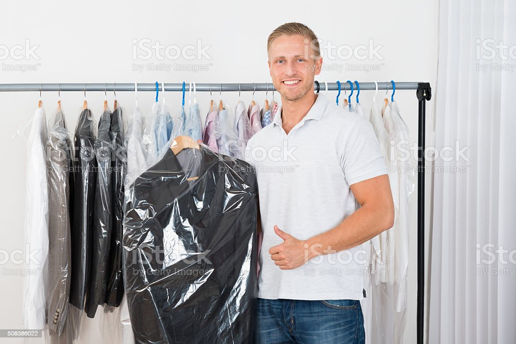 Young Man With Coat In Dry Cleaning Store stock photo
