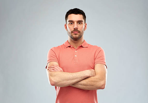young man with crossed arms over gray background stock photo