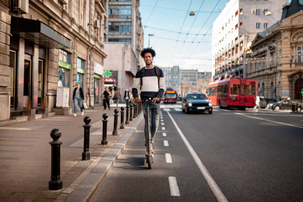 Young man with curly hairstyle riding an electric push scooter around the city stock photo