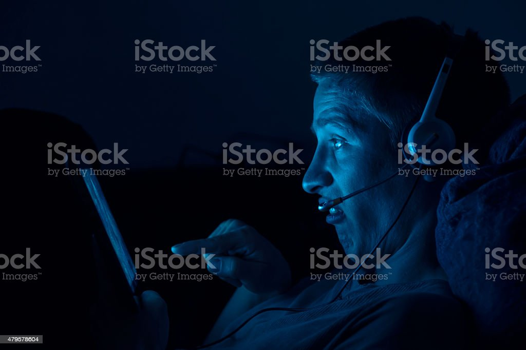 Young man with digital tablet at night stock photo