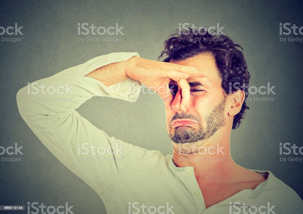 young man with disgust on his face pinches nose, something stinks stock photo
