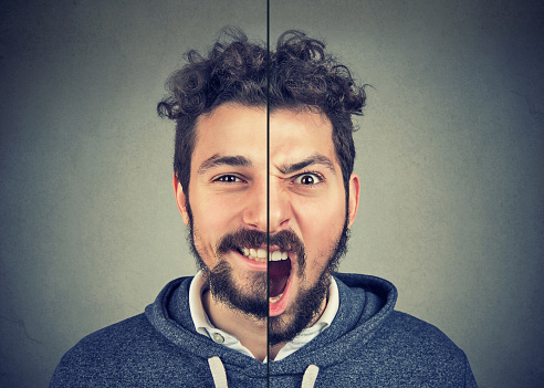 istock Young man with double face expression 916863524