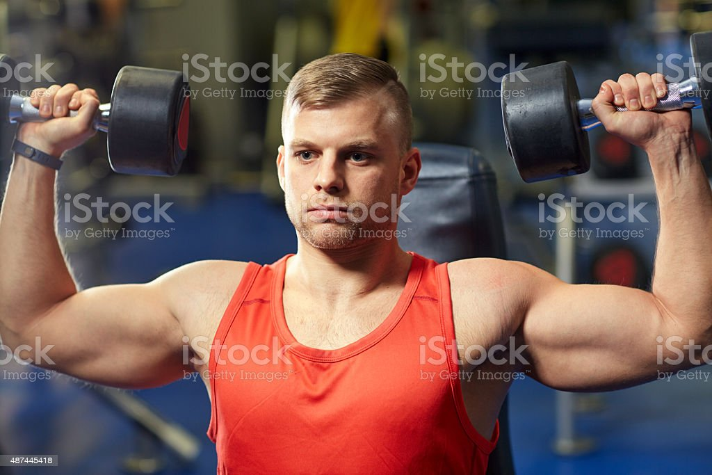 young man with dumbbells flexing muscles in gym stock photo