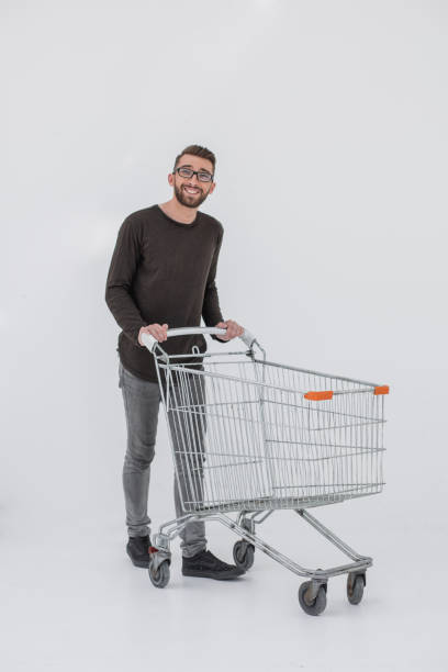 Young man with empty shopping cart, isolated on white stock photo