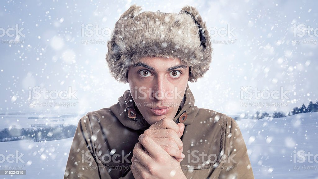 young man with eskimo hat and winter  background with snow stock photo