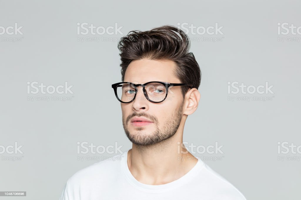 Young man with eyeglasses Close up portrait of young man with beard wearing eyeglasses looking at camera against grey background 25-29 Years Stock Photo