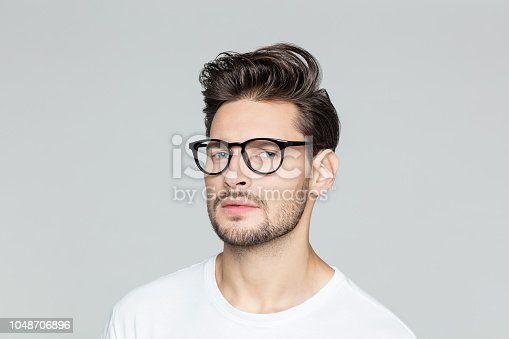 Close up portrait of young man with beard wearing eyeglasses looking at camera against grey background