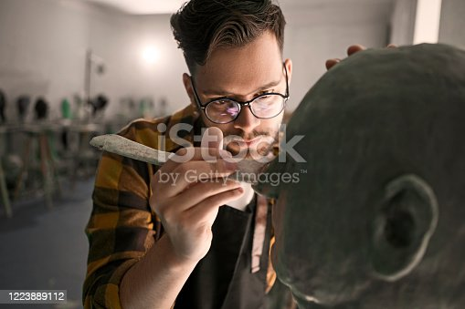 Young man sculpting head out of clay