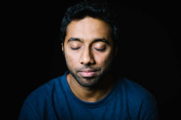 junger mann mit geschlossenen augen auf schwarzem hintergrund - augen geschlossen stock-fotos und bilder
