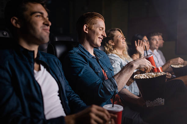 young man with friends watching movie in cinema - jacob ammentorp lund stock pictures, royalty-free photos & images