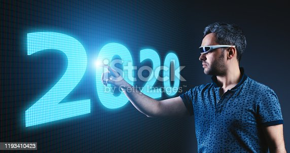 625727674 istock photo Young man with futuristic glasses touching imaginery screen on new year 2020 1193410423