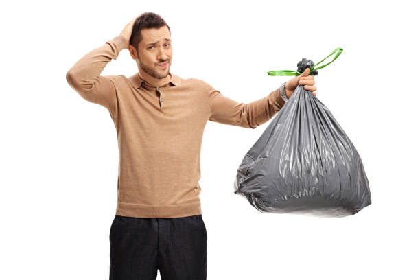 Young man with garbage bag holding his head in disbelief stock photo