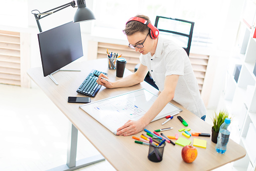 1133176165 istock photo A young man with glasses and headphones stands near a computer desk, holds a marker in his hand and prints on the keyboard. Before him lies a magnetic board and markers. 959961034