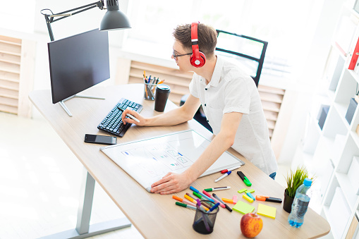 1133176165 istock photo A young man with glasses and headphones stands near a computer desk, holds a marker in his hand and prints on the keyboard. Before him lies a magnetic board and markers. 968086382