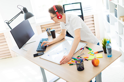 1133176165 istock photo A young man with glasses and headphones stands near a computer desk, holds a marker in his hand and prints on the keyboard. Before him lies a magnetic board and markers. 977976590