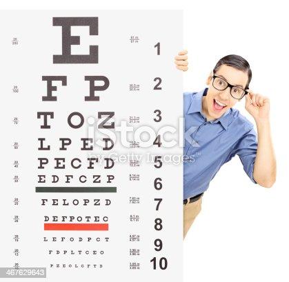 istock Young man with glasses peeking behind eyesight test 467629643