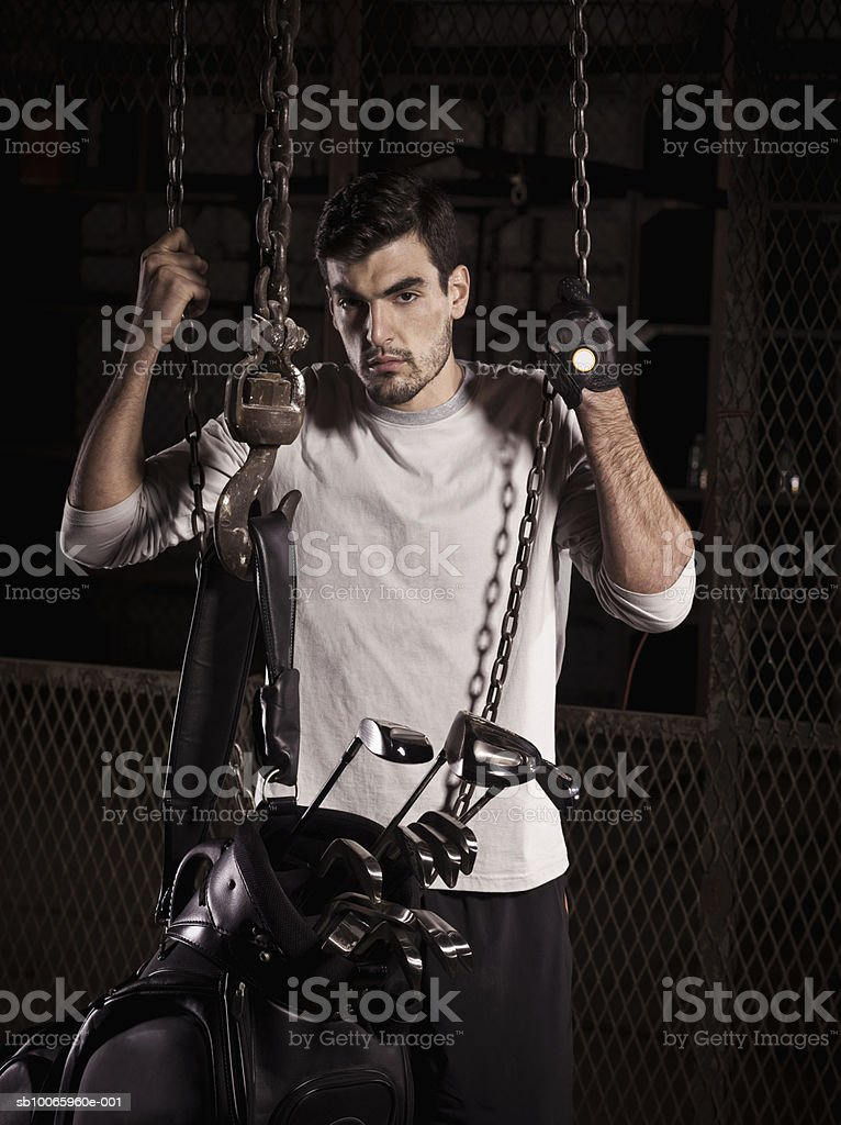 Young man with golf bag in abandoned factory, portrait royalty-free stock photo