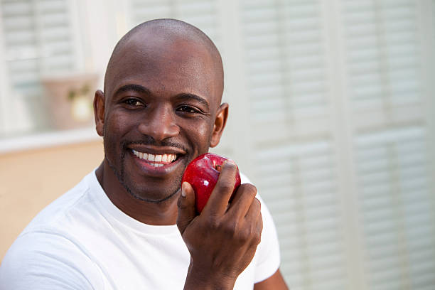 Young man with great teeth eating a juicy red apple stock photo