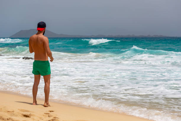 A young man with green swimming trunks walking stands on the sand while looking at a beach of Fuerteventura, Canary Islands, Spain stock photo