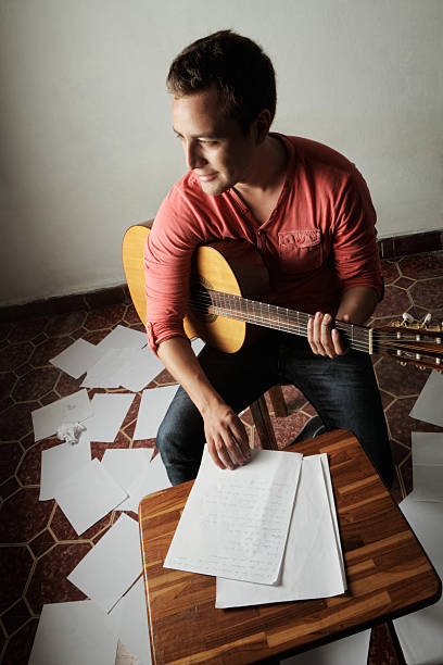 young man with guitar composing song - happy indie pop bildbanksfoton och bilder