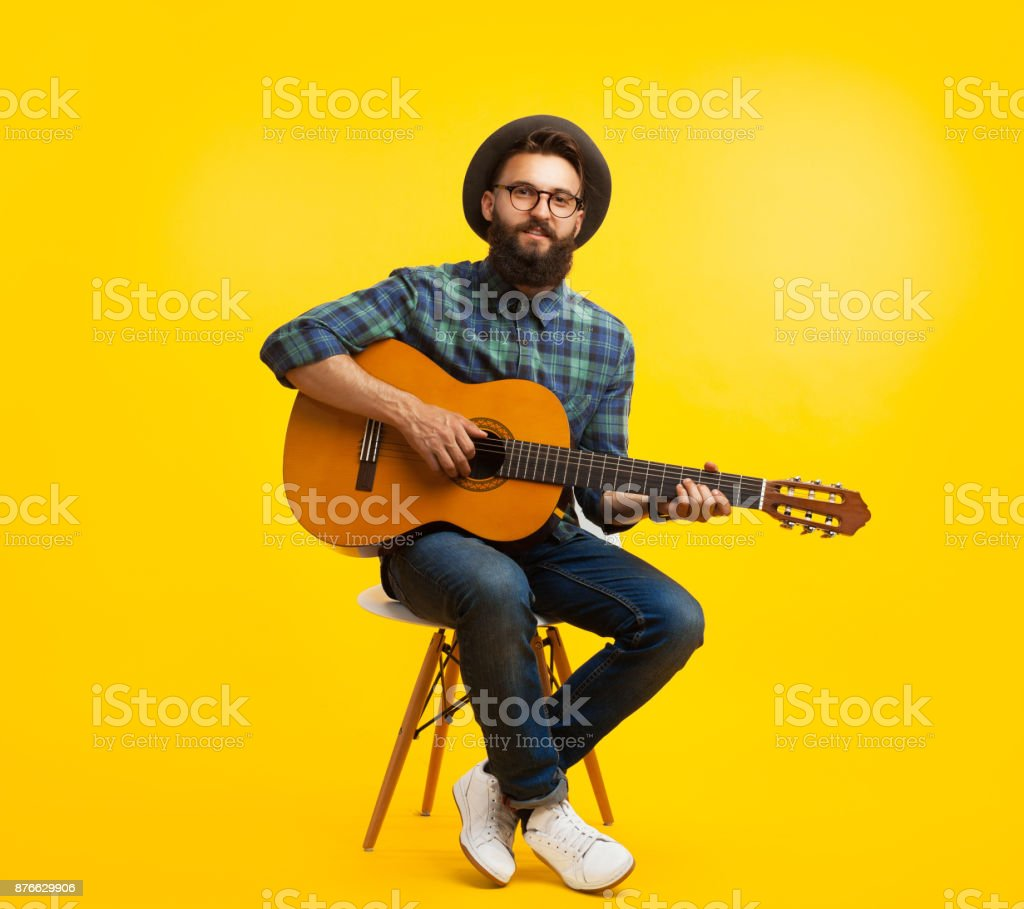 Young man with guitar in studio stock photo