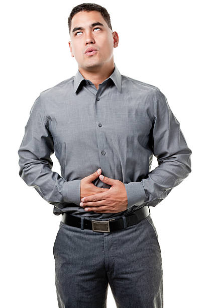 Young Man With Hands On Stomach Portrait of a man on a white background.http://s3.amazonaws.com/drbimages/m/jamle.jpg rolling eyes stock pictures, royalty-free photos & images