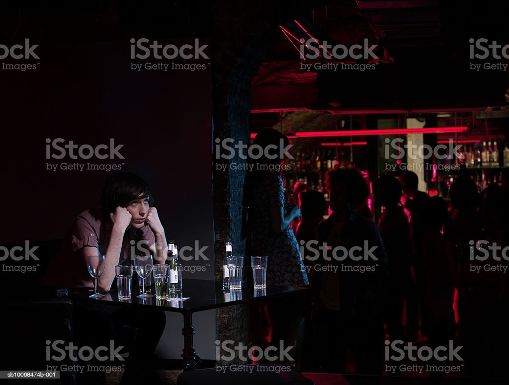 Young man with head in hands sitting at table in bar royalty-free stock photo