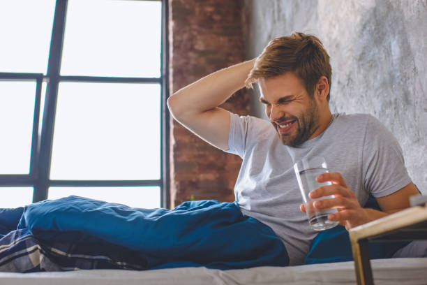young man with headache holding glass of water in bed at home young man with headache holding glass of water in bed at home aftereffect stock pictures, royalty-free photos & images