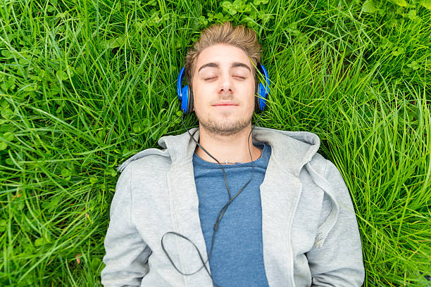 Young man with headphone listening to music in park stok fotoğrafı