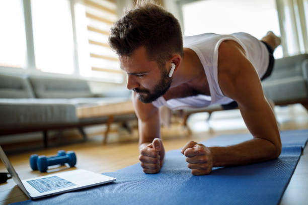 Young man with headphones using laptop for exercising at home stock photo