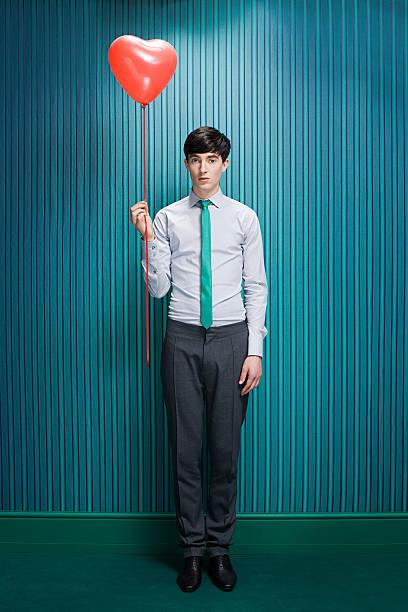 junger mann mit herzförmigen ballons - ballonhose stock-fotos und bilder