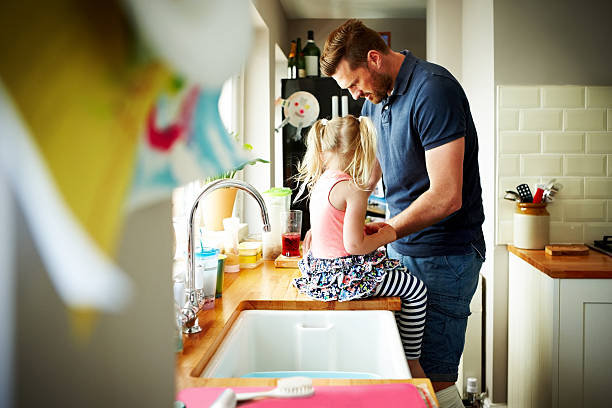 Young man with his daughter preparing lunch in kitchen Young man preparing lunch with his daughter sitting on kitchen counter stay at home father stock pictures, royalty-free photos & images