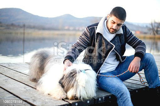 Young man with his dog on wood pier near lake looking the view