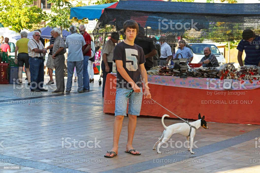 Young man with his pet in the market in Besalu